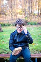 little boy with glasses and book in hand smiles -pleasure to read outdoors.