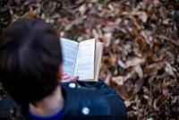 little boy reads a book leaning against a tree-pleasure of reading outdoors.