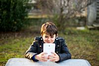 little boy with tablet smiles and looks at the screen.