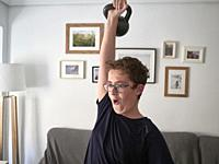 Teenager (boy) training at home with a kettlebell during the enclosure in the covid-19 pandemic. Valencia city, Valencia, Spain.