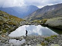 Middle age woman hiking on Lliterola valley near a small tarn, Benasque, Aragón, Spain.