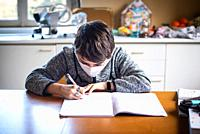 12 year old boy writes homework in notebook, mask on his face.