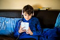 12 year old boy listens to music sitting on the sofa with tablet in hand.