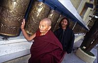 Tibetan monk at Namgyal monastery with prayer wheels and tenzin in the background, Mac leod Ganj, HP, India.