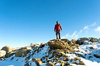 A man with red jacket looking at the top of a snowy mountain in Winter Long Shot with copy space success concept.