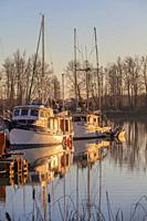 Winter sunset on commercial fishing vessels docked in Steveston Harbour British Columbia Canada.