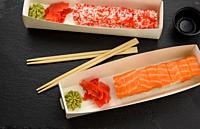 california sushi with red tobiko caviar and slices of philadelphia sushi with eel in a white box, delivery, top view.