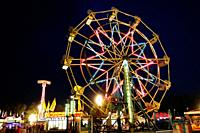 Ferris wheel at a carnival at night during a festival.