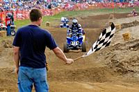 Contestent takes the checkered flag as he crosses the finish line in a off road ATV race.