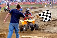 Checkered flag signals the end of the race at an ATV All Terrain Vechiles off road motocross type of race.