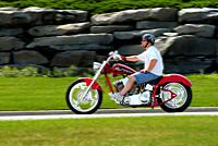 Male wearing protective helmet riding a red motorcycle for pleasure.