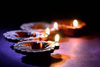 Colorful clay Diya (Lantern) lamps lit during Diwali celebration. Greetings Card Design Indian Hindu Light Festival called Diwali.