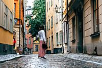Beautiful young woman is looking back in a picturesque and narrow cobblestoned street amidst old buildings in Gamla Stan quarter in Stockholm.