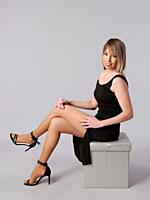 Young and pretty woman poses sitting with short black dress on gray background.