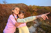 The girl hugs her sister who points her finger into the distance.