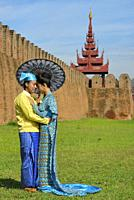Myanmar, Mandalay, Newly weds wearing traditional dresses posing before the royal palace.