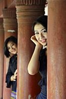 Myanmar, Mandalay, Young beauties posing between the the royal palace columns.