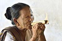 Myanmar, Bagan, Shwezigon pagoda, Old lady lighting a cheeroot (cigar).