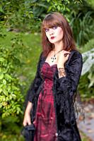 An 18 year old brunette woman wearing a costume in a garden setting looking directly at the camera.