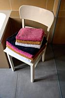 Interior scene, bathroom, stack of folded towels on vintage white chair near bathtub and shower glass