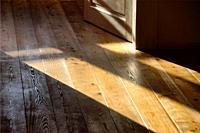 Old fashion interior scene, open wooden door, sunshine on wooden floor