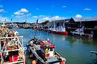 Fishing boats tied up in the harbour at Whitstable, Kent, England.
