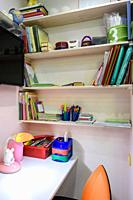 Writing desk in the children's room, view of the shelves for school books.