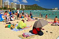 Sunbathers take up nearly all of the available sand at Waikiki Beach in Hawaii.