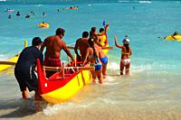 Adventures prepare to embark on an outrigger canoe trip from the shores of Waikiki Beach in Hawaii.
