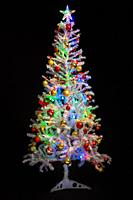 Festively decorated artificial white Christmas tree on a black background.