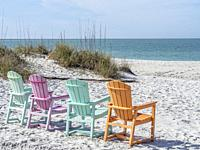 Colorful chairs on the Gulf of Mexico beach at the South Beach Bar & Grill in Boca Grande on Gasparilla Island Florida.