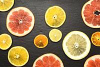 citrus fruits cut into round pieces: orange, grapefruit, lemon, tangerine. Ripe and juicy fruits on black background.