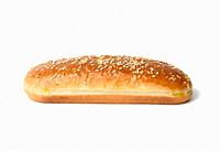 baked oval hot dog bun, baked goods sprinkled with sesame seeds and isolated on white background.
