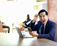 Portrait of Asian Businessman celebrate and glad for his success in cafe using smart phone and laptop with business team in background using for copor...