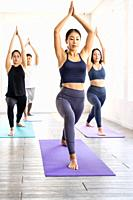 Group of young sporty attractive asian people practicing yoga lesson on Warrior and crescent pose with instructor coach in front in gym studio. Workin...
