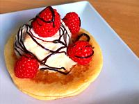 Pancakes with ice cream, raspberries and chocolate syrup.
