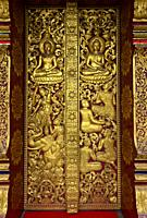 Entry portal with gilded carvings depicting mythical creatures and scenes from the life of Buddha, Temple Wat Nong Sikhounmuang, Luang Prabang, Laos.