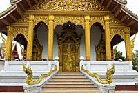 Gilded carvings at the main portal and mythological Naga snake on the banister, Temple Wat Nong Sikhounmuang, Luang Prabang, Laos.
