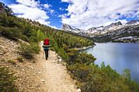 Backpacker above South Lake, John Muir Wilderness, Sierra Nevada Mountains, California USA.