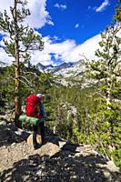 Backpacker on trail in the John Muir Wilderness, Sierra Nevada Mountains, California USA.