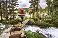 Backpacker crossing creek in the John Muir Wilderness, Sierra Nevada Mountains, California USA.