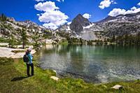 Hiker on the shore of Treasure Lake, John Muir Wilderness, Sierra Nevada Mountains, California USA.