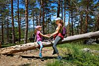 Woman mother and daughter, seven years old girl, with hat, playing sitting on tree trunk in pine forest of Guadarrama Natural Park (Madrid, Spain).