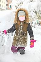 Seven years old child with coat, winter knitted hat, gloves and face mask walking in snow, in street of Madrid city, Spain.