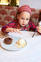 Seven years old girl is going to touch a scoop of vanilla ice cream with chocolate coulant with her finger, in nice ceramic plate, on white tablecloth...