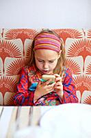 Seven years old cute girl with hairband, sitting in red sofa, watching with a surprised face a smartphone mobile in her hands.