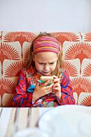 Seven years old cute girl with hairband, sitting in red sofa, watching with anfry face a smartphone mobile in her hands.