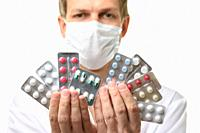 A man in a medical mask holds a fan of medicines in front of him, focusing on medicines.