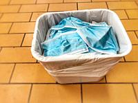 waste basket full of discarded disposable face masks