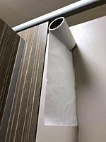 Roll of toilet paper at the top of a toilet door
